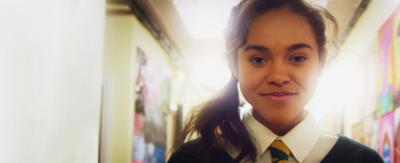 A girl in school uniform in a corridor smiling as she is surrounded by bright light, Polly.