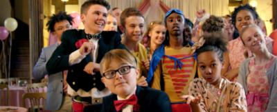 A group of boys and girls stand together in various poses at a wedding.