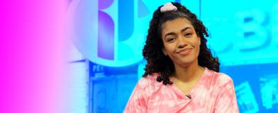 "Alishea on CBBC HQ set with a purple tint and a logo saying ""Dance Club"""