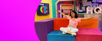 Alishea on the set of CBBC HQ with her arms out stretched.