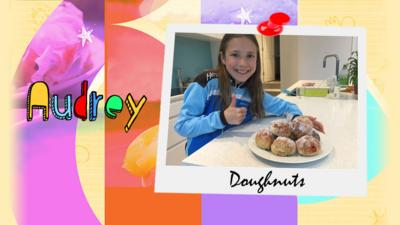 A girl shows a plate of doughnuts that she has made.