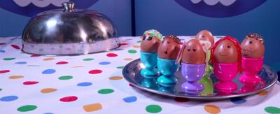 A selection of decorated eggs on a serving tray. The eggs have faces drawn on them, and hair made from sprinkles, and strawberry laces.
