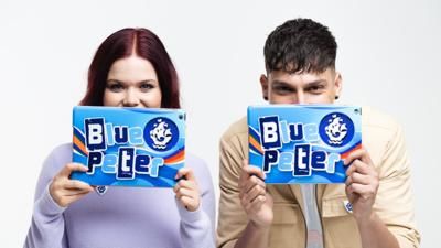 Blue Peter presenters Lindsey Russell and Richie Driss hold tablets in front of their mouths.