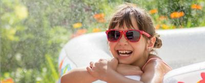 A girl wearing sunglasses out in the garden.