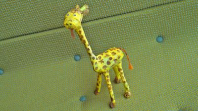 The giraffe in full, stood on a green textured background.