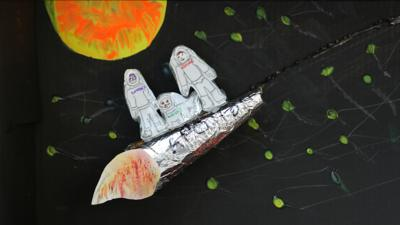 A model of the Apollo 11 space ship, made from a super glue bottle wrapped in foil, with paper drawings of Richie, Lindsey and Henry stood on top.