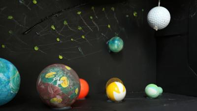 Six planets, and the moon. The moon is made from a golf ball, and the planets made from bouncy balls and polystyrene.