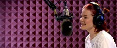Lindsey, wearing headphones, speaking into a microphone.