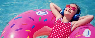 A girl relaxing in an inflatable donut lilo, floating on a swimming pool.