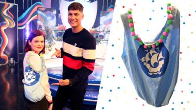 Blue Peter presenters Lindsey and Richie pose with a tote-style bag made from a t-shirt, decorated with the Blue Peter logo and pom poms.