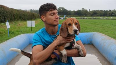 Blue Peter presenter Richie holds a muddy Henry, the Blue Peter Dog.