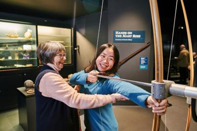 A girl uses a longbow at the Mary Rose Museum