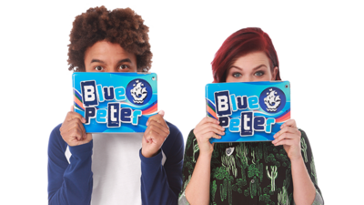 Radzi and Lyndsay hiding behind blue cue cards with the Blue Peter logo on them.