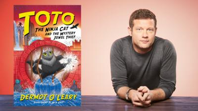 Dermot O'Leary on a red background with a copy of his book 'Toto The Ninja Cat'