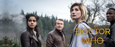 A woman with short hair; Doctor Who, stands with three friends in a forest.