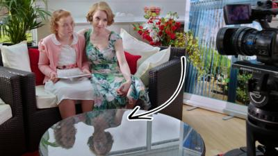 Floss from the Dumping Ground sat on a sofa with a woman. There is an arrow pointing at the woman's reflection in the glass table in front of them