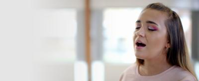A headshot of Lauren Platt singing in a hall.