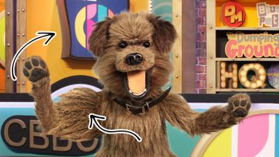 Hacker standing in the CBBC HQ studio. There is an arrow pointing to his arm and one pointing to the background
