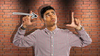 Karim standing in front of a wall and there is an arrow pointing to the shadow on the wall behind him