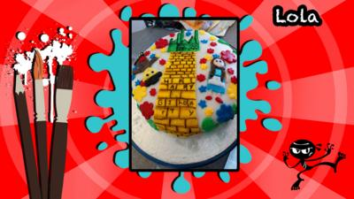 A birthday cake decorated with a picture inspired by the Wizard of Oz's yellow brick road.