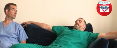 Dr Xand lying on a sofa while Dr Chris looks at him.