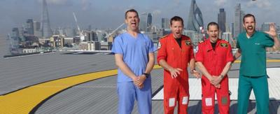 Dr Xand and Dr Chris standing with two medical professionals. They are all pulling faces and are standing on a helipad, on the  top of the roof and next to a helicopter.