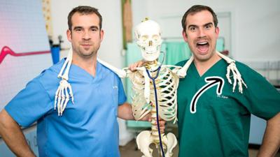 Dr Chris and Dr Xand posing with a skeleton. There is an arrow pointing at the skeleton's hand
