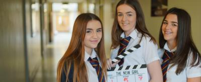 Our School student holding a clapper board