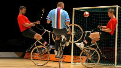 A man on a bicycle scores a goal between two defenders also on bicycles.
