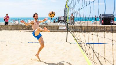 A man volleys a ball in the air playing footvolley on the beach.