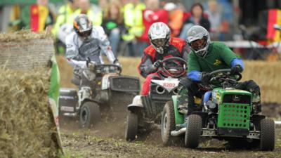 Three lawnmower racing drivers competing in a sit on lawnmower race.