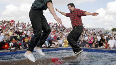 Two men compete to knock each other off a log in a log rolling competition.