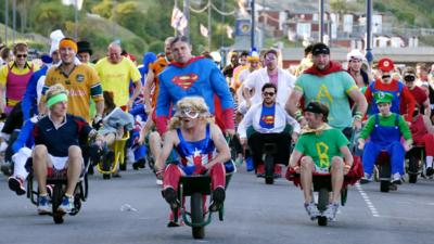 People race in fancy dress for a wheelbarrow racing competition.
