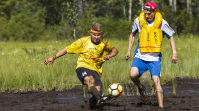 Two footballers covered in mud attempt to kick a football in a swamp.