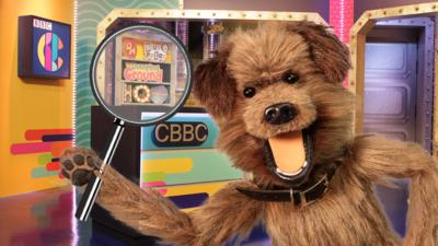Hacker in the CBBC HQ studio holding a magnifying glass