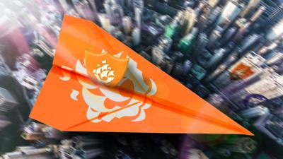 An Orange Blue Peter badge on an orange paper aeroplane, flying over a city.