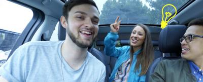 Three people in a car laughing.