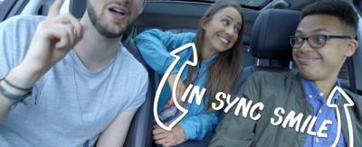 Rebecca Jackson and Sideways Sid in a car with an 'In Sync Smile'.