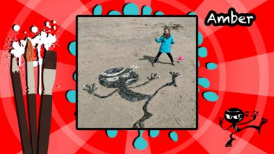 An Art Ninja character made in pebbles on a beach.
