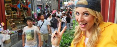 Naomi Wilkinson showing a 'peace' sign with her fingers on an Asian street.