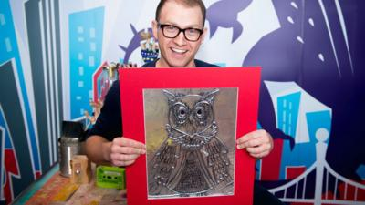 Ricky with an owl picture made out of tin foil.
