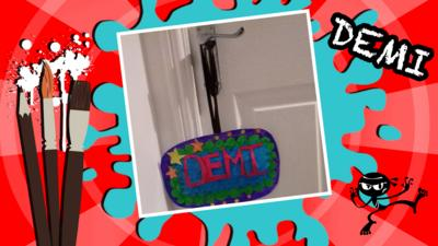 A pop art room sign for a door handle, which says 'Demi'.