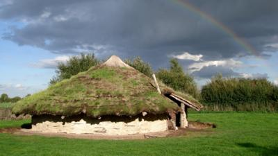 A Bronze Age roundhouse in a field with a rainbow cutting through the dark clouds in the background