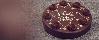 Chocolate cake with Blue Peter written on it in icing.