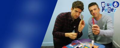 Greg James and Chris Smith holding up lollystick superheroes with the Blue Peter logo next to them.