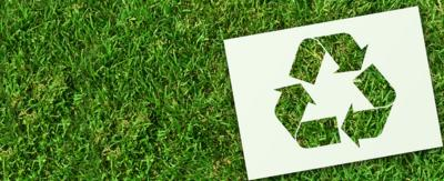 A recycling symbol laying in the grass.