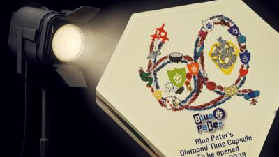 The diamond time capsule logo under a spotlight.
