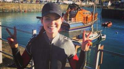 Lindsey in a wet suit in front of a lifeboat