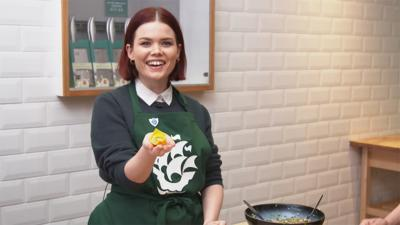 Lindsey is wearing a green Blue Peter apron and is holding out a wonton to the camera.