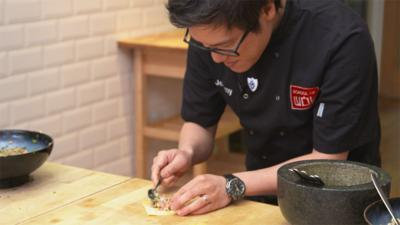 Jeremy Pang from School of Wok fills the wonton pastry on a kitchen table.